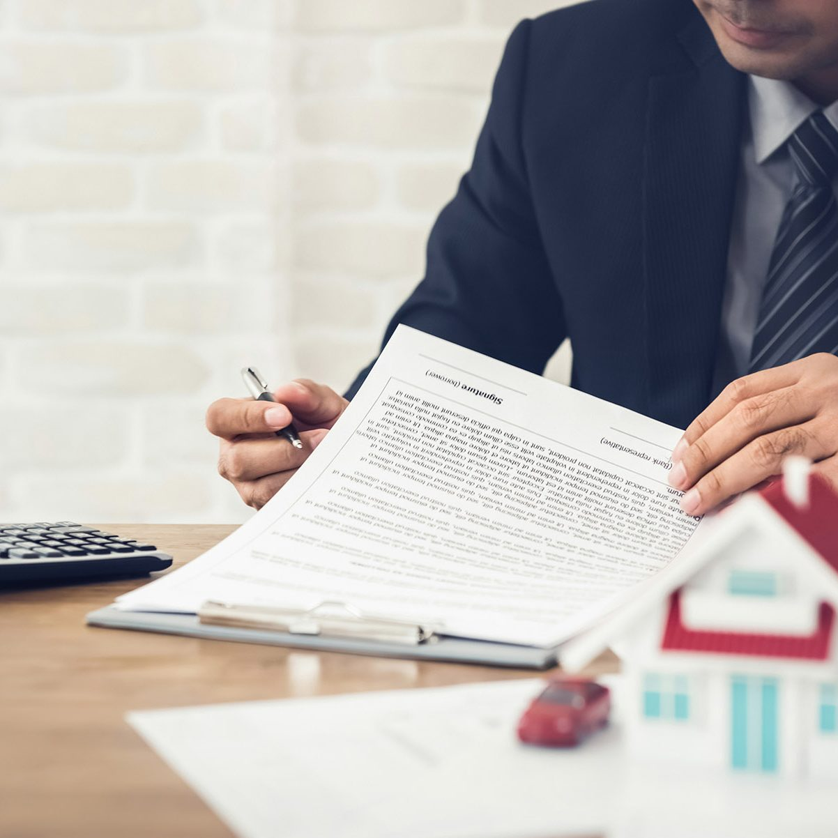 Businessman as a property agent or investor calculating growth of return on investment in real estate before signing contract at the office